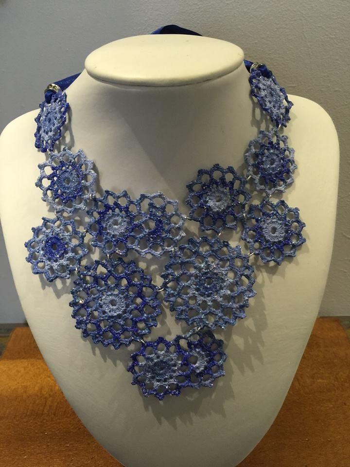 collana all'uncinetto effetto pizzo a pettorina,dipinta a mano nei toni dei blu/azzurro,con forme tonde di varia dimensione ,assemblate da anellini argentati.Glitter in tinta e vetrificati.Chiusura in raso blu con perle argentate