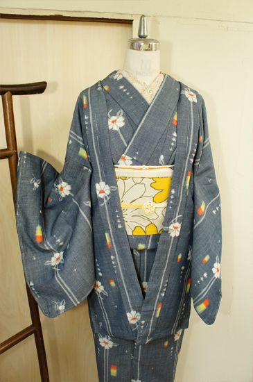 シャーベットのようなパウダーがかったグレーに近いネイビーに、またたく星のような十字模様や、オレンジ・黄色・若草緑のトリコロールモチーフ、可憐なお花ストライプが織り出されたレトロキュートなウールのアンサンブル(羽織と着物のセット)です。