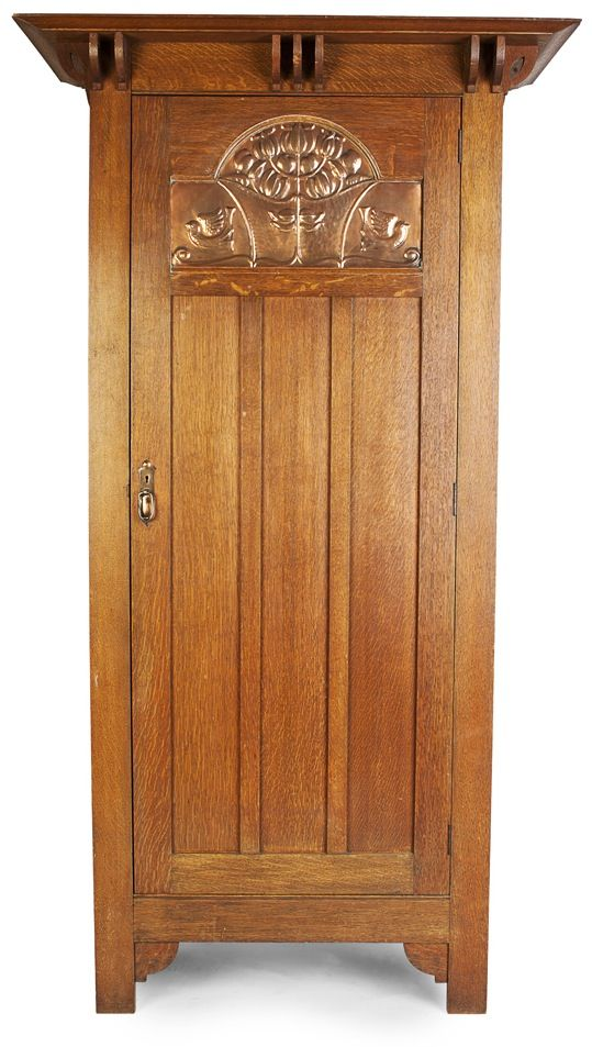SHAPLAND & PETTER, BARNSTAPLE  ARTS & CRAFTS OAK HALL CUPBOARD, CIRCA 1900,  the projecting cornice above a single door with copper panel repoussé decorated with flying birds and a stylised shrub motif,  107cm wide, 199cm high, 57cm deep  |  SOLD £475 Oct. 29, 2014