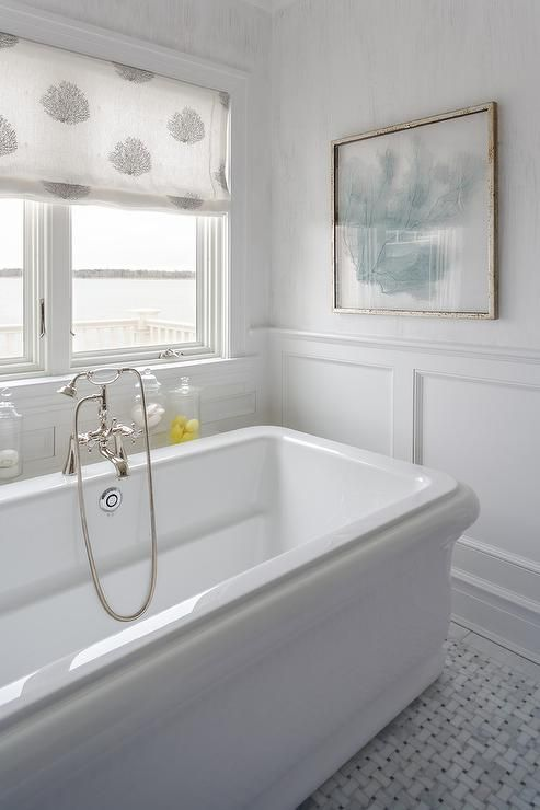 Beautiful beach style cottage bathroom boasts a Waterworks Empire Freestanding Rectangular Bathtub paired with a polished nickel vintage hand held bathtub filler and positioned on marble basketweave floor tiles beneath a window dressed in a black and white sea fan roman shade.