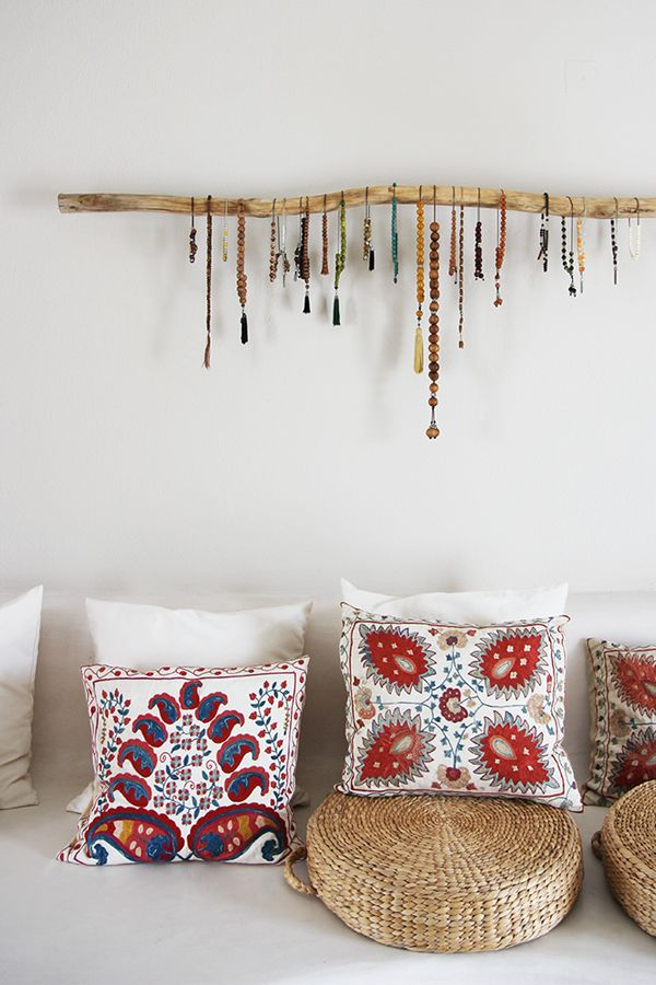 Are those Buddhist prayer malas hanging on that branch as art? Pillows are gorgeous; Suzani embroidered silk