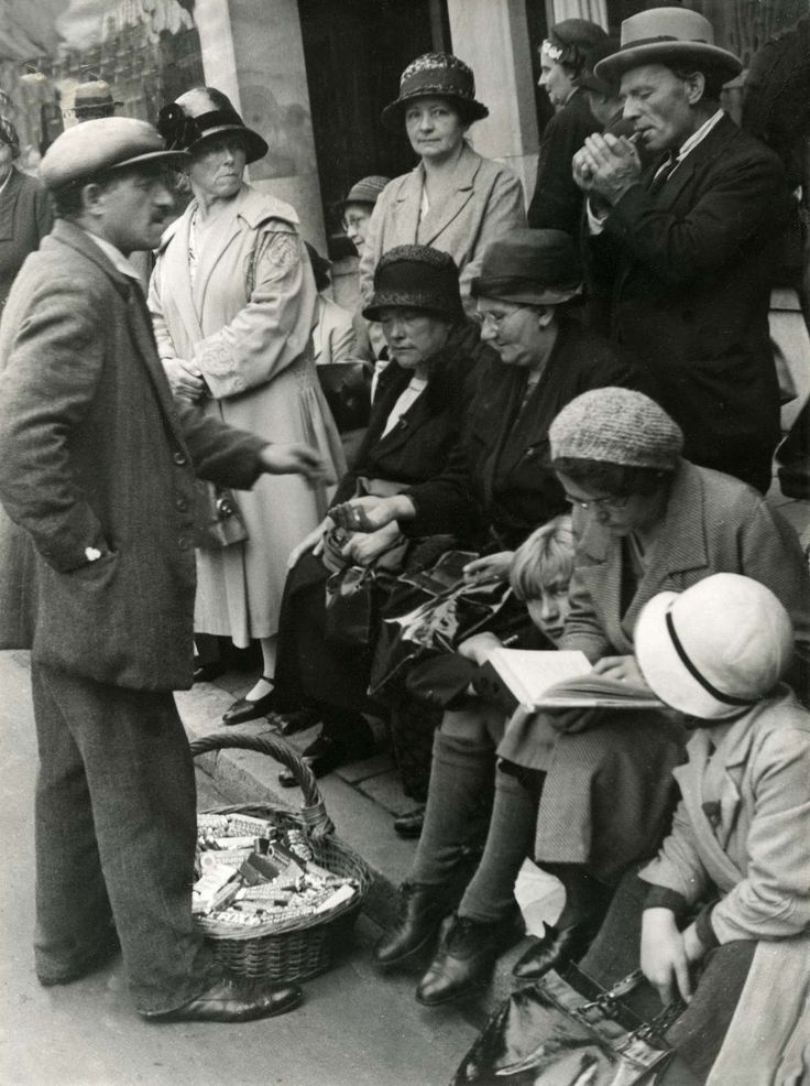 Straathandelaar met mand vol snoep, verkoopt aan wachtende mensen die langs de straat zitten, Nederland 1925.
