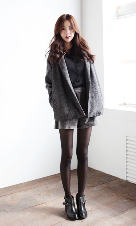 Simple winter outfit with the large grey coat, black tights, grey skirt, black top, and black boots.