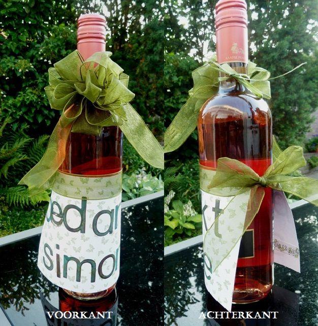 Een aangeklede fles wijn. Benodigdheden: papier, lint en letter stempels.