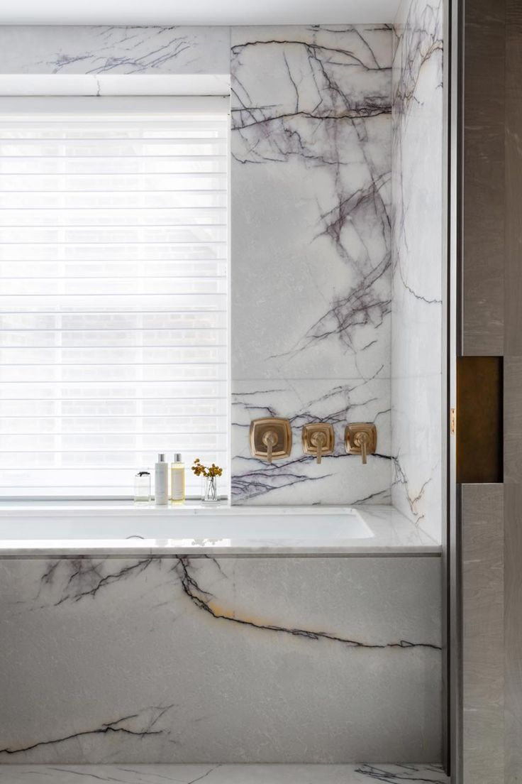 a black and white marble bathroom with white window shadings and warm brass fixtures by caballero