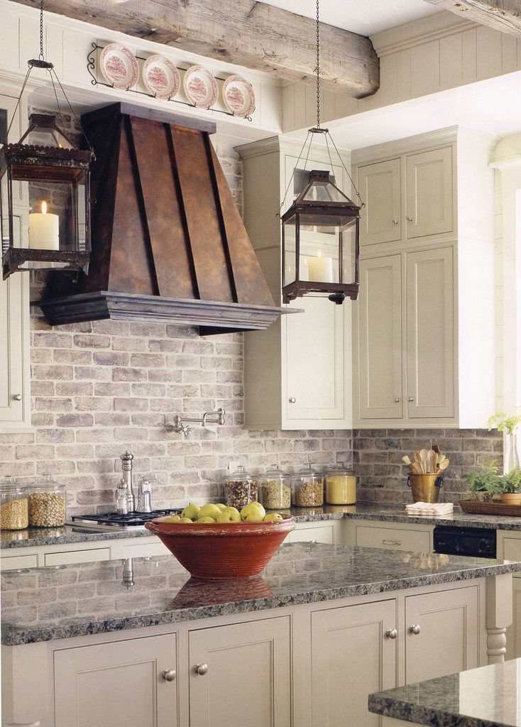 Love this rustic kitchen with brick back splash copper vent hood and lantern pendant light fixtures over the island gorgeous exposed beams add extra