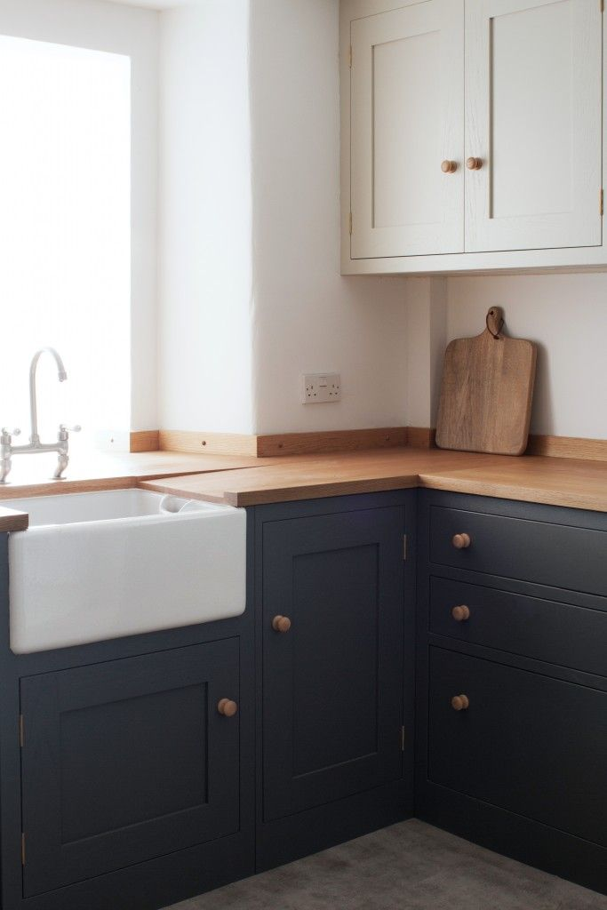 Farmhouse sink with Astbury bridge tap surrounded by an oak worktop create the perfect country feel in this shaker style oak kitchen. The base units are painted in Farrow & Ball Down Pipe while the wall units are painted in Farrow & Ball Shaded White.