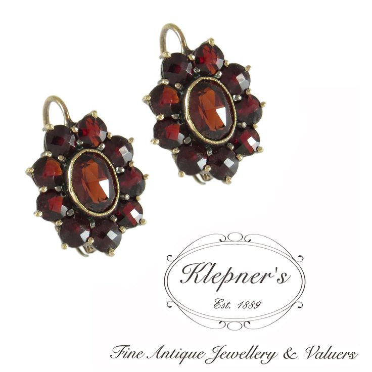 8ct yellow gold antique Edwardian Bohemian garnet cluster earrings, centrally set with two oval rub set pyrope garnets & eighteen round rose-cut pyrope garnets. The earring are finished with hinged European hook fittings. Visit us at www.klepners.com.au