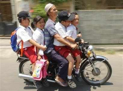 A motorcycle taxi driver takes four children home from school, Wednesday, Sept. 8, 2004, in Jakarta, Indonesia. To make transportation more affordable, albeit more dangerous, students usually pile onto motorcycles for their commute home.