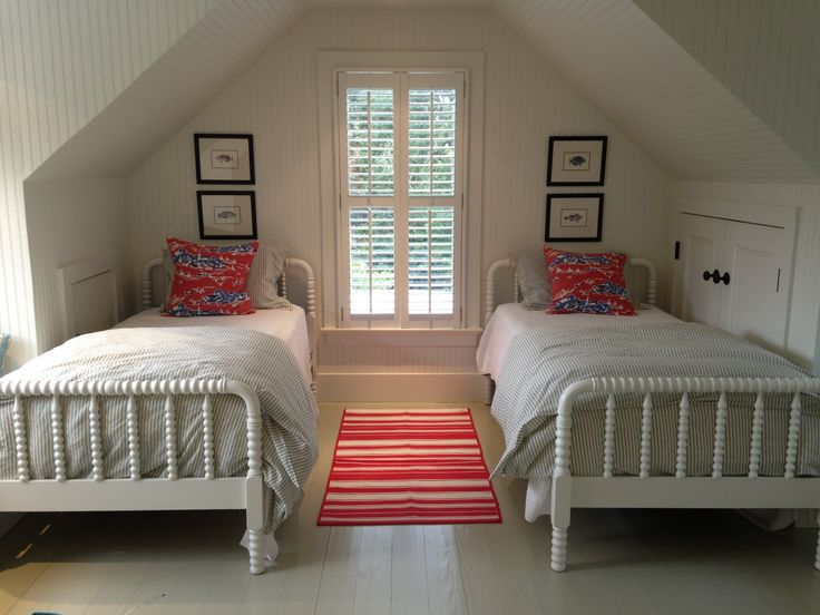 Refinished twin beds for boy's room with blue ticking duvet and red accent pillows and striped rug.