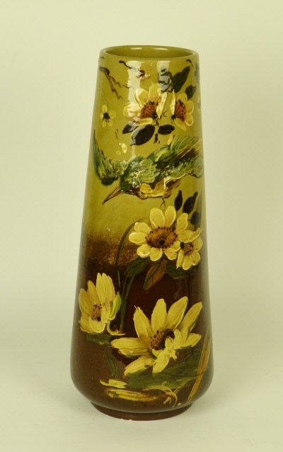 An Art Pottery vase signed 'Dean' the tapering cylindrical vase enamelled with a flying bluebird amongst blossom and flowers, glazed in tones of ochre, brown, green and blue, signed 'Dean', 42.5cm high  Sold for £110   ANTIQUES & WORKS OF ART WELSH BRIDGE SALEROOMS 9 February 2011