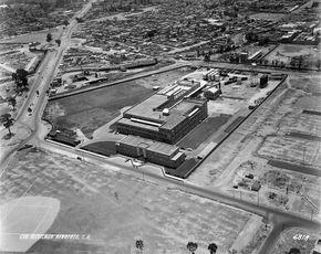 Una toma aérea de 1950 donde destaca en el centro la fábrica de Colgate-Palmolive, con la calle de Presa La Angostura al frente y la Calzada Legaria del lado izquierdo. En el terreno de abajo hoy se encuentran los laboratorios del SAT y el Centro de Investigación en Ciencia Aplicada y Tecnología Avanzada del IPN. Se puede ver al fondo el cauce del río San Joaquín, y a la izquierda, una parte del Panteón Francés. A la derecha apenas se está trazando la colonia Irrigación. La vista es hacia el…