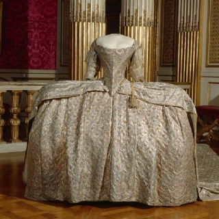 Marie Antoinette's dress on display at Versailles.I'd never be able to walk in that thing, let alone try to sit!!