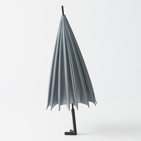 This umbrella by Japanese studio Nendo has a two-pronged handle that allows it to stand on its own when not in use.