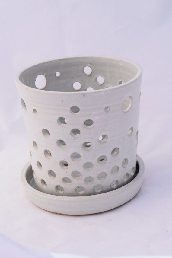 This pot features drainage holes all around the sides and bottom. Will keep your orchid happy and healthy! I throw each pot by hand on the wheel, and then alter afterwards with different sized hole punches. This pot and matching saucer are both glazed in a simple white glaze.
