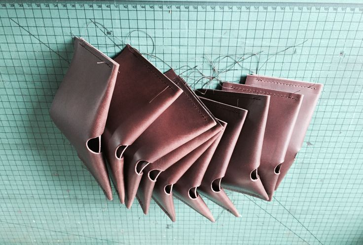 Snaking their way across the workbench are the first ten Origami wallets from this order, stitched up and ready for trimming and bevelling, then a dab of beeswax to aid the burnishing process... and on to the next ten