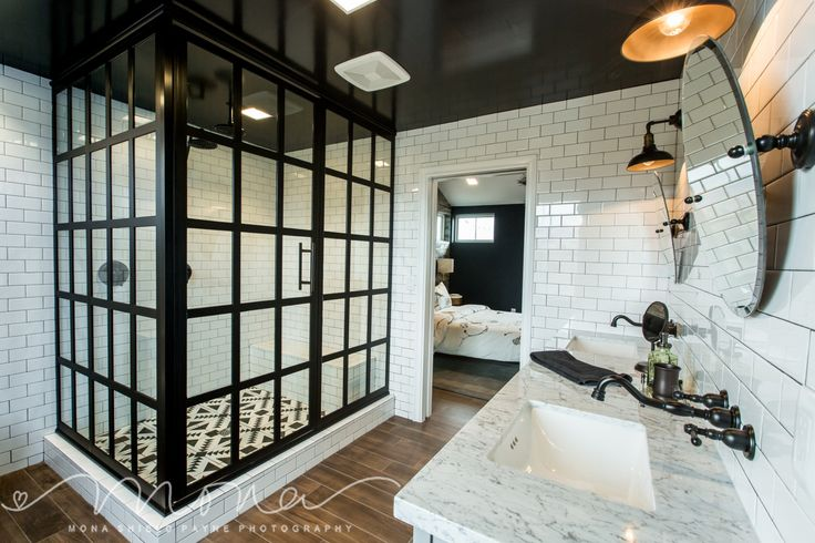 The master bathroom of our Modern Farmhouse features a black and white canvas with uses of warm woods on the floor and modern tribal tiles in the shower.