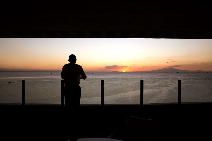 """Nov. 19, 2015 """"The President watches the sun set over Manila Bay from his hotel balcony in Manila."""" (Official White House Photo by Pete Souza)"""