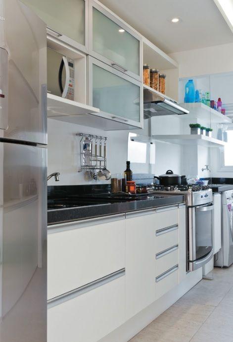 O uso de cores claras e prateleiras para decoração de espaços pequenos. Neste ambiente, a porta de correr foi eliminada de modo que a iluminação natural da lavanderia chegasse também até a cozinha.