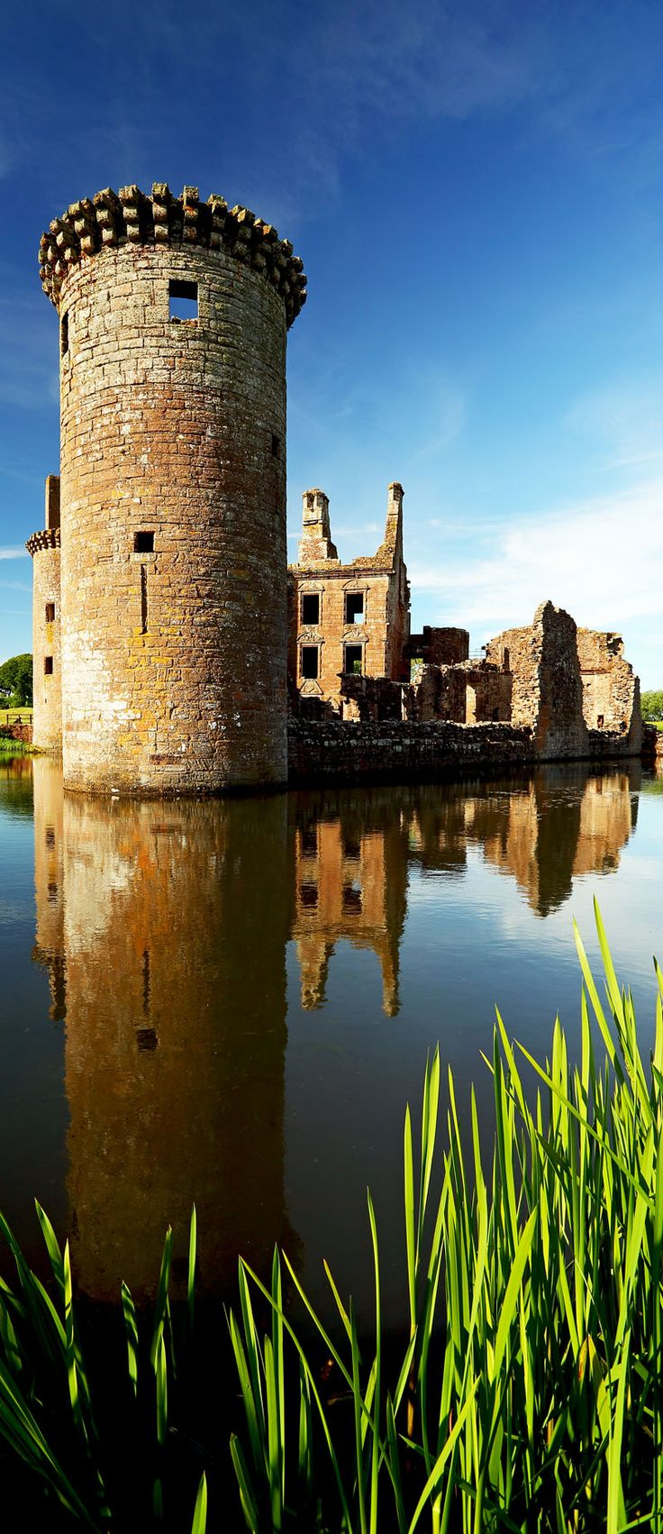 Caerlaverock Castle reflecting on the moat that surrounds the castle in Dumfrieshire, Scotland.