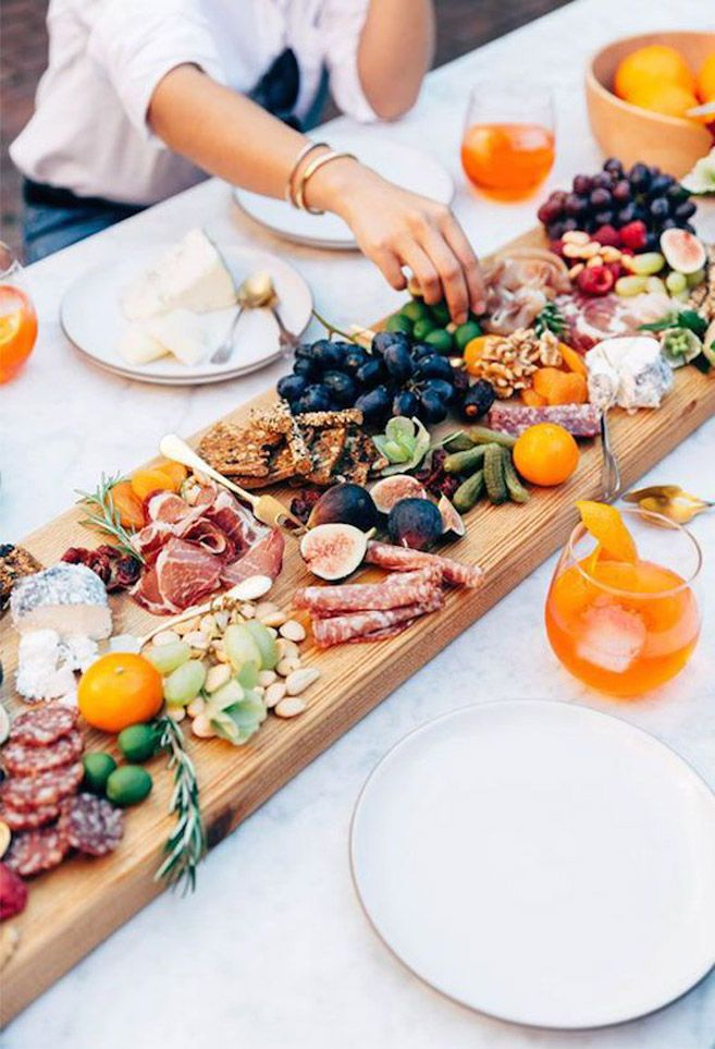 Forget flowers and centrepieces, your guests will definitely appreciate a food-focused tablescape like this one featuring a super long charcuterie spread.