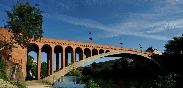 despontsentreleshommes:  Le pont Neuf ou de la Libération dans leLot-et-Garonne. Le pont Neuf ou de la Libération de Villeneuve-sur-Lot est à l'époque de sa mise en service, en 1920, le premier pont en arc en béton non armé atteignant une portée de plus de 96 m. Conçu parEugene Freyssinet, ses deux arcs, tout en courbe, supportant le tablier, s'enfoncent, en effet, dans les fondations au-dessous de l'étiage.