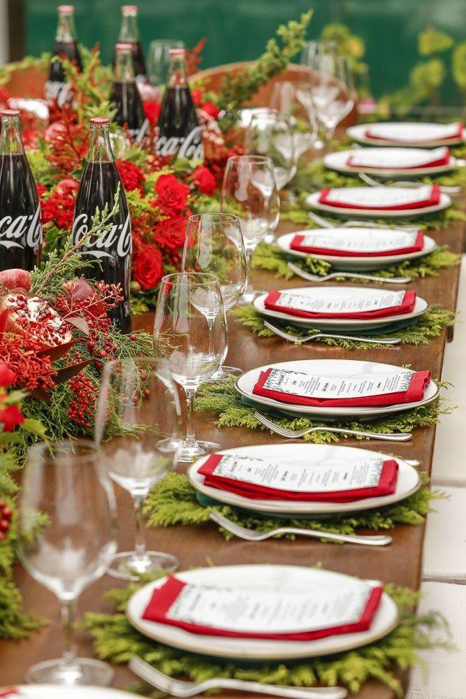 Sobre as mesas, louças brancas com friso dourado, talheres em prata, jogos americanos feitos de tuia natural (já ensinamos o passo a passo, aqui), guardanapos vermelhos e taças transparentes, delimitavam o lugar de cada convidado.
