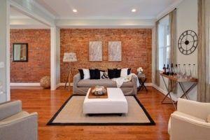 Unverputzte Ziegelwände und lackierten Holzböden machen das Wohnzimmer lebendig werden. Foto von StruXture Fotografie