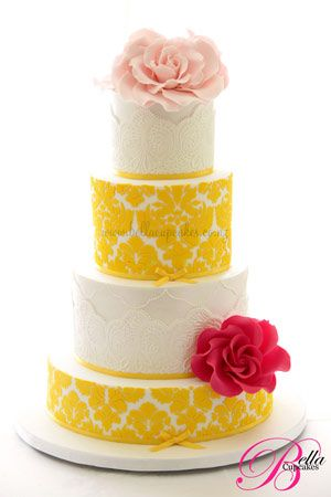 Alternating tiers of embossed (or raised --- I'm not quite sure of the technique here but it's glorious) brocade 'fabric' in yellow and white. Trimmed out with two tones of pink roses. Surprising combo but I dig it. Fun yet elegant!