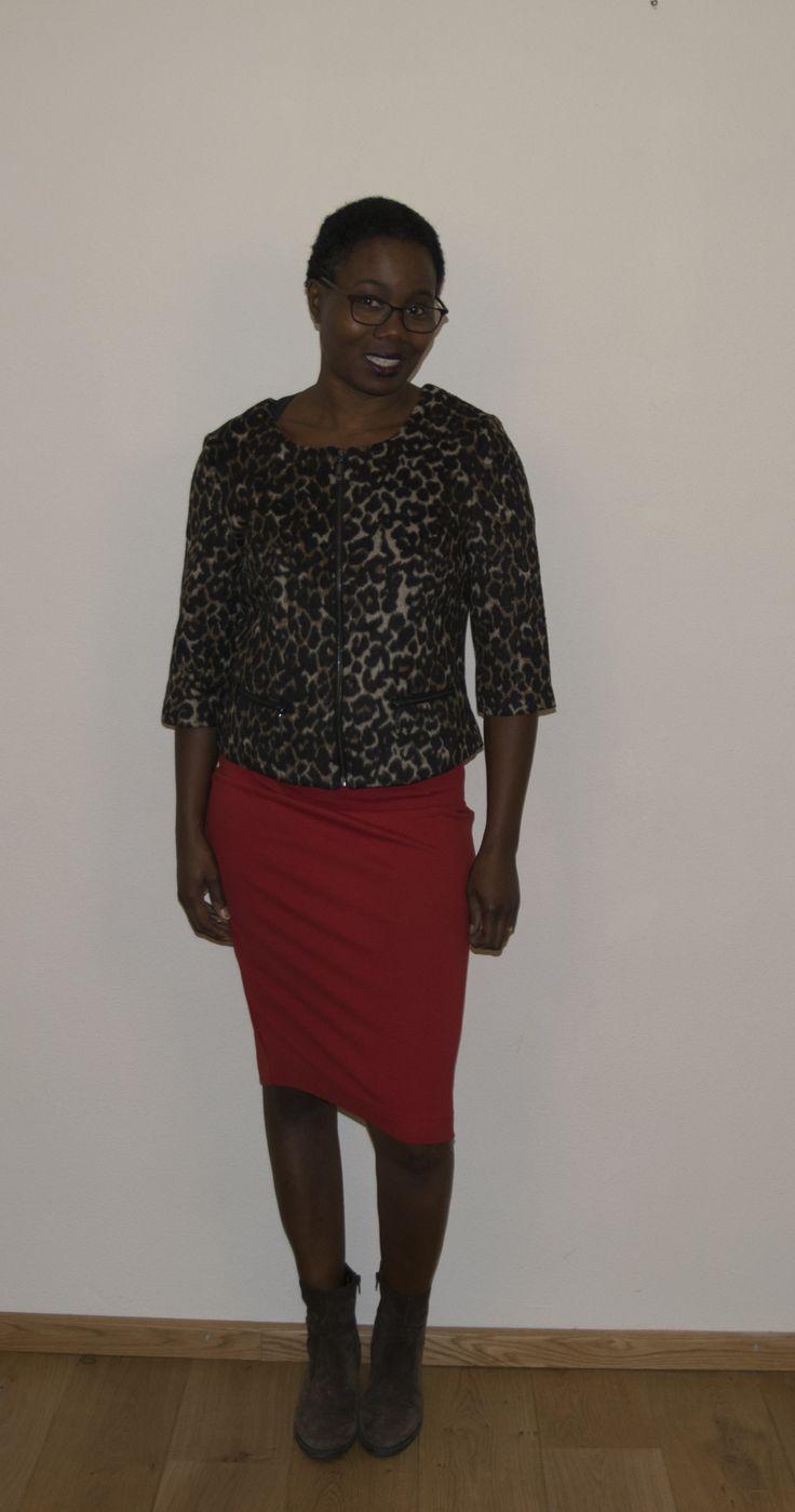 Een oranje kokerrok met het wollen vestje in jaguarprint. Daaronder draag ik een bruin, kort, suède laarsje. De oranje rok draag ik om het geheel een vrolijker accent mee te geven.