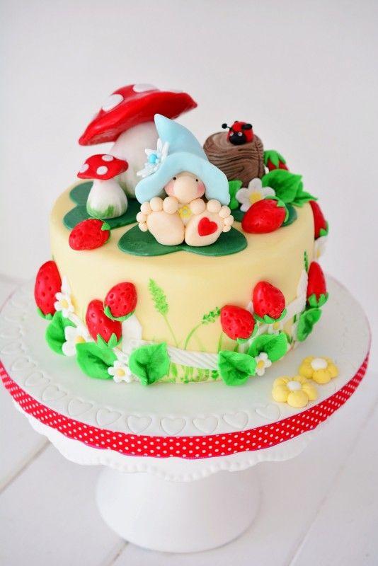 Eine Motivtorte mit dem Thema  Märchenland, in dem lustig gepunktete Pilze sprießen, ein kleiner Marienkäfer ein Päuscheln einlegt und saftig rote Walderdbeeren zum Naschen einladen.