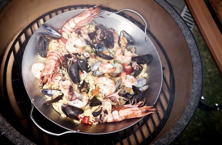 Paella op de Big Green Egg houtskoolbarbecue. Op het gietijzeren grillrooster kun je makkelijk een pan kwijt.
