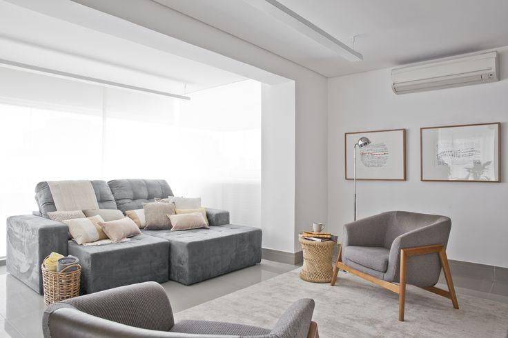 Sala de estar e tv branca e cinza. Sofá e piso de porcelanato com poltronas de design, luminária, plantas e quadros compõe o ambiente.