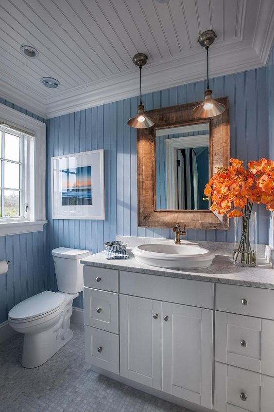 Coastal bathroom with blue and white motif. Blue bead board walls bring New England charm into this bathroom, while a Carrara marble vanity top and accent pieces add a touch of elegance!