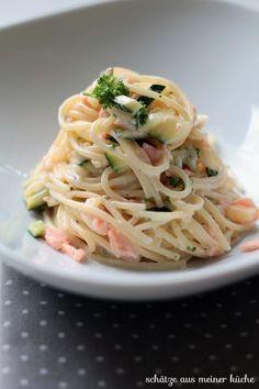 Zucchini-Lachs-Spaghetti《 Für 2 Portionen《 250 g Spaghetti《 1 kleine Zucchini (gelb oder grün)《 1 kleine Zwiebel《 1 Knoblauchzehe《 100 g Räucherlachs《 125 ml Sahne《 2 EL Créme Fraîche《 2 TL Zitronensaft《 2 TL Olivenöl《 etwas frisch, gehackte Petersilie《 Salz & Pfeffer