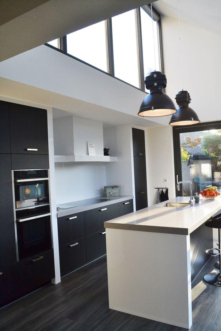 Prachtige ruimte voor deze mooie zwart/witte keuken met betonlook blad.