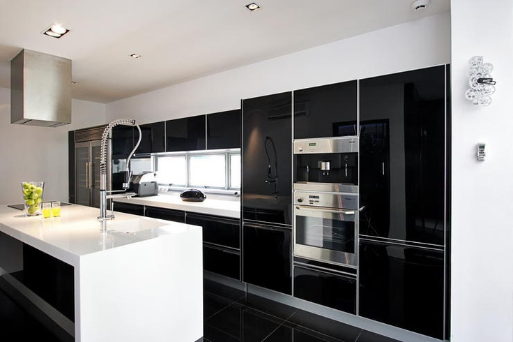 Minimalistic kitchen in black and white with marble counter tops and glossy cabinets.