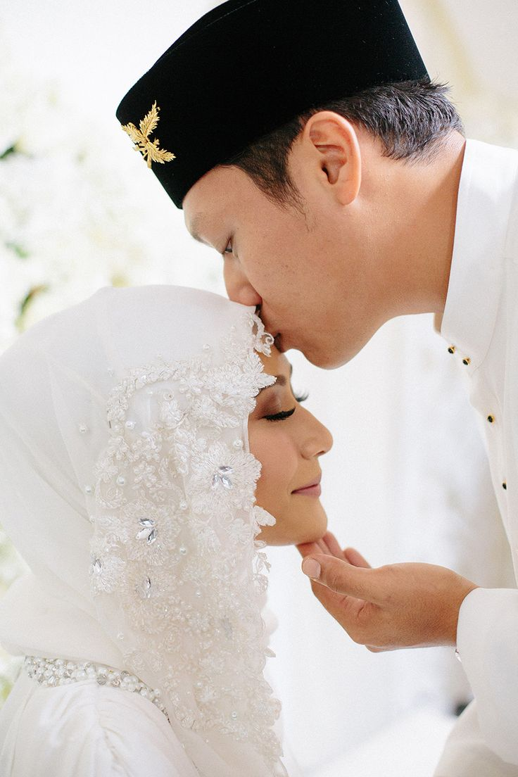 Bride and groom sharing an intimate kiss during their solemnisation ceremony looking resplendent in all white traditional Malay costume from Adila Long // Razif and Sarah decided to celebrate their Singapore wedding solemnisation, or nikah, at Ba'alwie Mosque in a meaningful and intimate ceremony captured by Zakaria Zainal of We Made These.