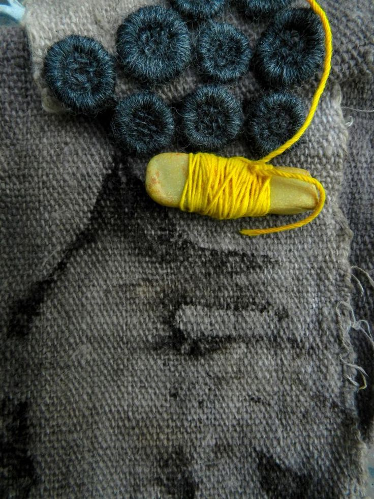 stone wrapped tumeric dyed embroidery thread on walnut dyed korhogo cloth