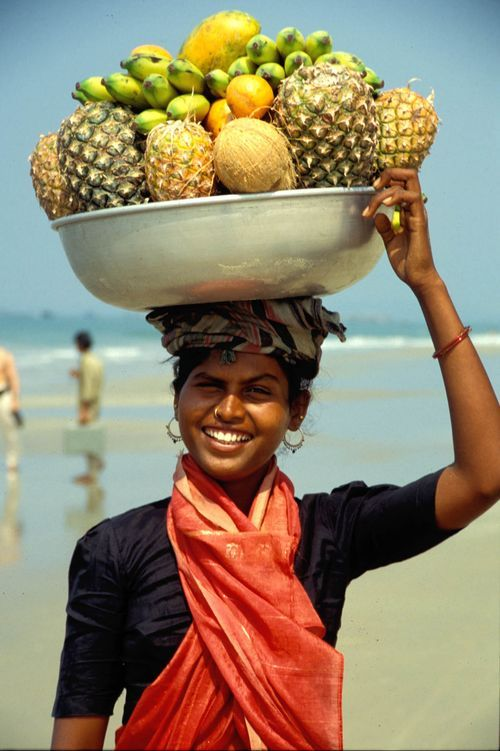 """Fruit vendor on the beaches of Goa in India. (It looks to me like her container is plastic. Again, as with cars, etc. someone might argue that we in """"the West"""" have been enjoying the privileges of plastic - light, inexpensive, easily used - for decades, so why shouldn't people around the world be able to do the same?)"""