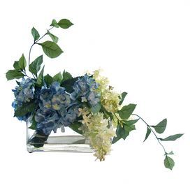 """Faux hydrangea and lilac arrangement in glass pot.   Product: Faux floral arrangementConstruction Material: Silk, plastic, acrylic and glass Color: Blue, green and white Dimensions: 14"""" H x 14"""" W x 9"""" D Note: For indoor use only"""