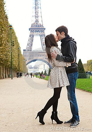 Young romantic couple kissing near the Eiffel Tower in Paris - minus the Eiffel tower.