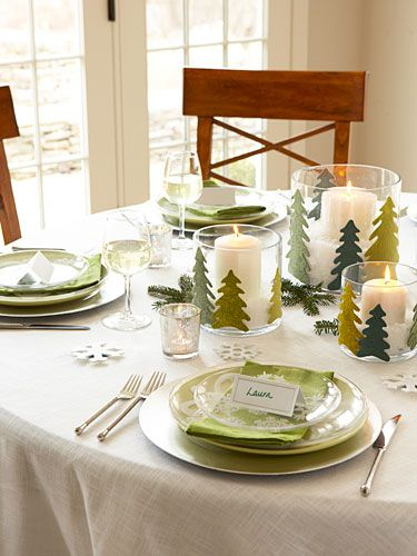 Turn your table into a winter wonderland with cut-out felt trees glued onto candleholders filled with faux snow. Place settings in a palette of white, green, and silver make the scene as serene as the snowdrifts outdoors.