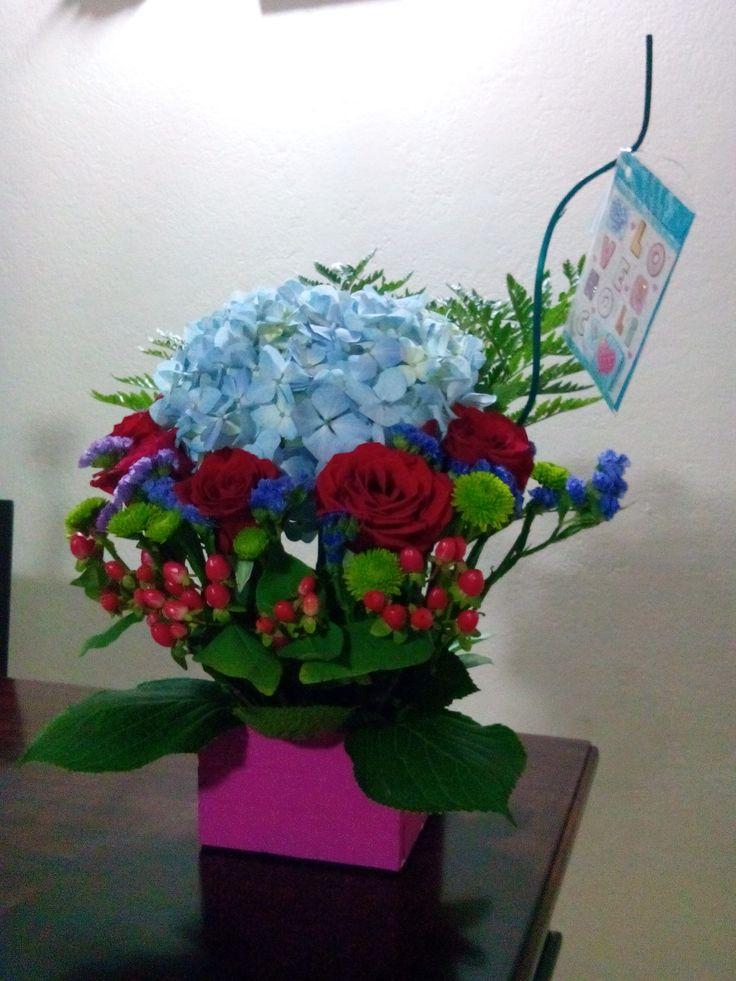 Arreglos florales, hortensia azul, pinochos, hipérico, rosas rojas, rusco.
