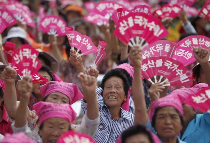 """Female farmers participate in a protest rally opposing the Free Trade Agreement (FTA) between South Korea and China in central Seoul. They also demanded the withdrawal of the FTA between South Korea and the U.S. according to local media. Fans read,""""Government purchase agricultural products!"""" (Kim Hong-Ji/Reuters photo)"""