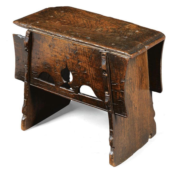 A rare English oak and elm boarded stool 16th century the moulded seat above pierced motifs to the aprons, the end board supports with projecting shaped buttresses, losses