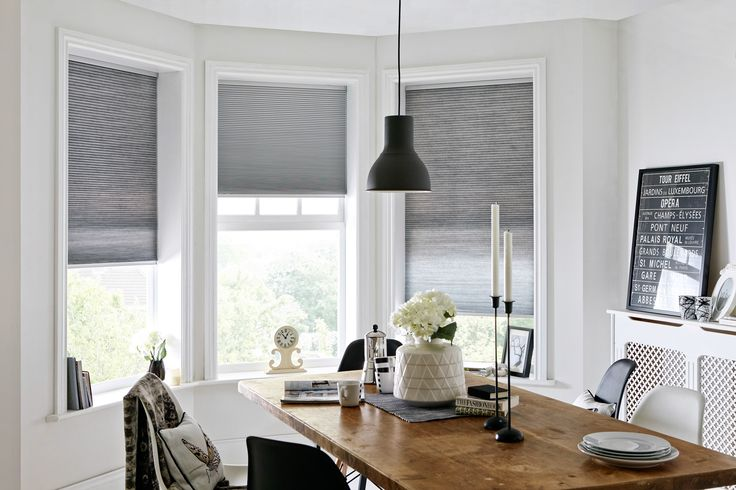 Achieve a pared-back look and embrace sustainable living with Hive® blinds by Style Studio. With a honeycomb structure that has heat-blocking and retaining qualities, they will help to save energy (and money) from the moment they're installed. Cool greys and white walls with a solid wood table complement the minimalist Scandi décor. Silver Hive Blinds.
