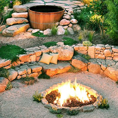 Backyard campfire A built-in firepit is the hub of gatherings in this garden. Sandstone cobbles edge the 5-foot-diameter lava rock–topped pit, which blazes with gas-fed flames. A sandstone wall, scattered with cushions for comfort, serves as seating. Thyme and other herbs grow around the firepit and between the seat wall's stones.