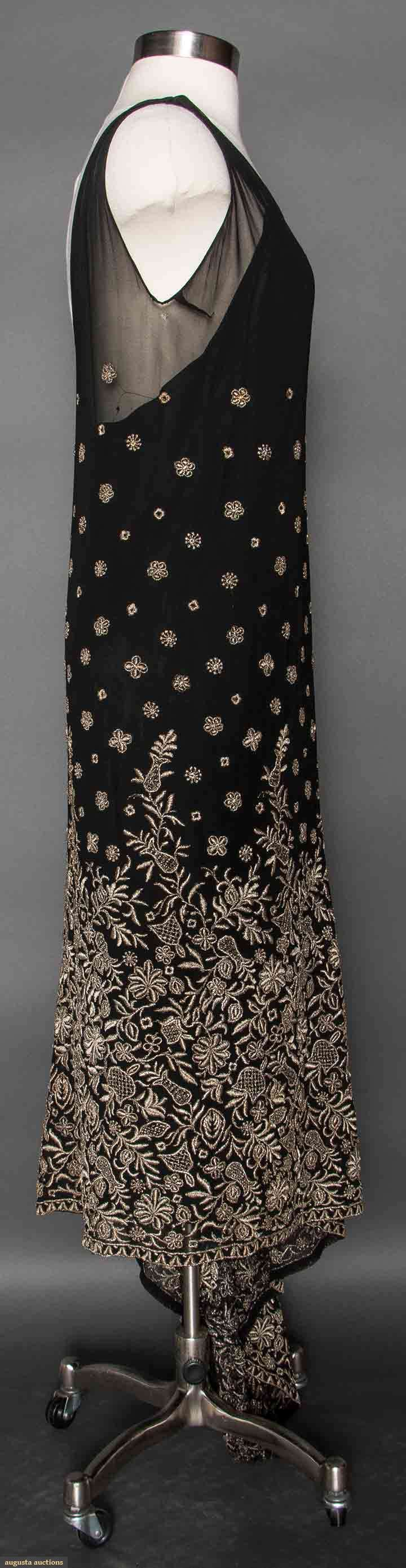 EMBROIDERED BLACK SILK DRESS, 1920s. Silk chiffon, sleeveless, angled hemline, bottom skirt half densely embroidered in metallic silver floral pattern. Sideway