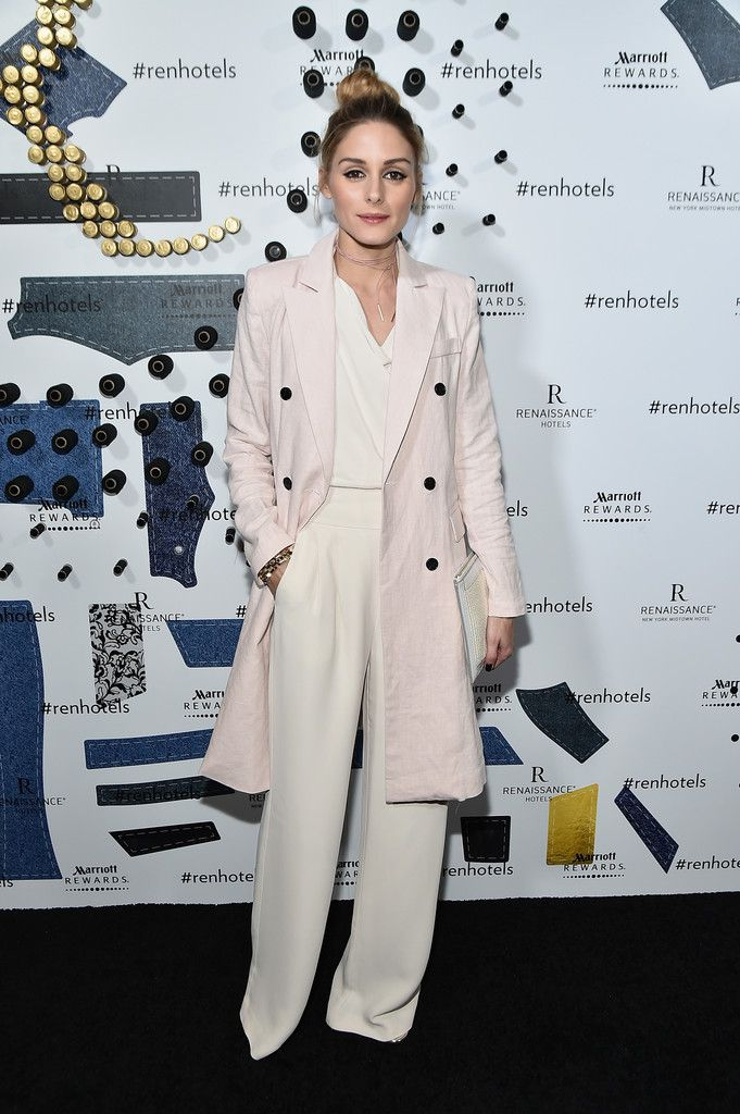 Olivia in a white wrap blouse with matching wide-leg pants that complemented her white clutch and a pale pink trench that matched her pink AdornMonde shoelace choker.